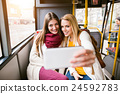 Beautiful young women traveling by bus, taking 24592783