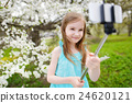 Adorable girl holding tulips in cherry garden 24620121