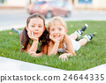 Two little girls in roller skates laying on the 24644335