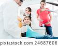 Dentist treating the whole family in his office 24687606