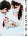Dentist treating woman patient with drill 24687609
