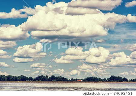 Waterfront with trees and house and blue sky 24695451