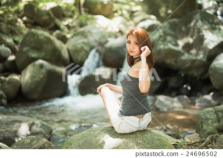 Asia beautiful young sexy girl sitting on a rock at water fall 24696502