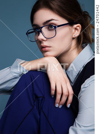 Businesswoman portrait with glasses and blue suit with hand under the chin 24701442