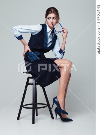 Businesswoman sitting on office chair holding glasses 24701445