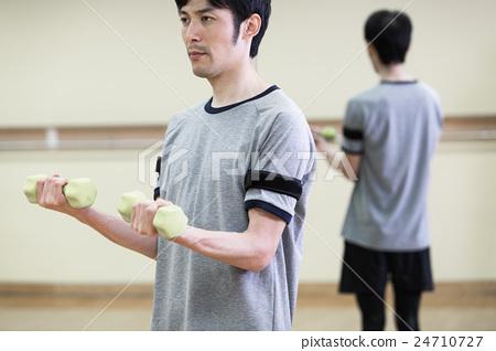 用壓力帶和啞鈴訓練手臂的男人 24710727