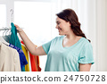 happy plus size woman choosing clothes at wardrobe 24750728