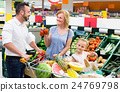 family shopping various fresh vegetables in supermarket 24769798