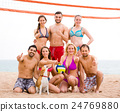Vacationers playing volleyball on beach 24769880