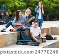 Portrait of four teenagers playing music together outdoors 24770246