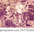 Portrait of four teenagers playing music together outdoors 24770260