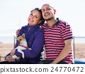 man, woman and dog on the beach 24770472