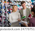 Couple trying items in the sport shop. 24770751