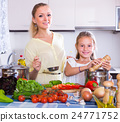 Woman and girl cooking veggies. 24771752
