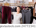 Young female brunette choosing trousers in shop 24772341