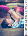 Asian boy taking photographs by camera.  24791024