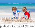 Two kid boys building sand castle on tropical 24793947