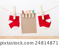 Blank paper with baby socks hanging on clothesline 24814871
