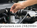 A mechanic is opening the oil cap  24820084