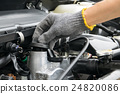 A mechanic is opening the oil cap 24820086