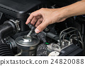 A mechanic is opening the oil cap  24820088