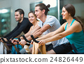 Group young working out of cycling in fitness club 24826449