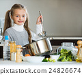 Cute little girl cooking veggies in kitchen 24826674
