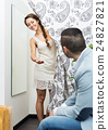 Young couple at fitting room. 24827821