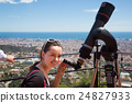 Woman looking in telescope on viewing point 24827933