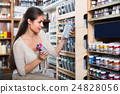 woman choosing paint in aerosol can in shop. 24828056