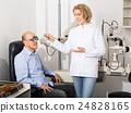Adult optician examinating eyesight 24828165