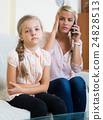 Worried mother calling doctor for daughter with abdominal pains 24828513