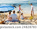 Couple relaxing on beach while their kids playing active games 24828783