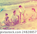 Laughing family of six people playing together on beach 24828857