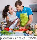 man and woman standing near table with vegetables 24829596