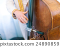 the man plays a contrabass. 24890859