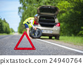 Woman changing tire after car breakdown 24940764