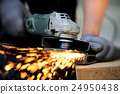 Worker cutting metal with grinder 24950438