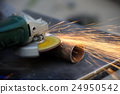Worker cutting metal with grinder 24950542