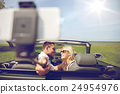 happy couple in car taking selfie with smartphone 24954976