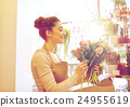 smiling florist woman making bunch at flower shop 24955619