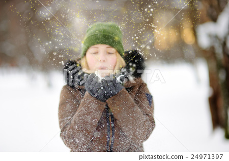 Outdoors portrait of young beautiful woman playing with snow 24971397