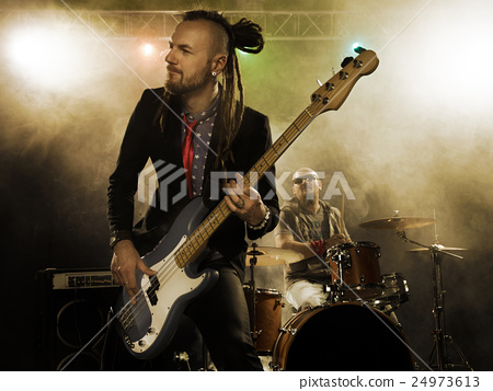 Rock band performs on stage. Bassist in the 24973613