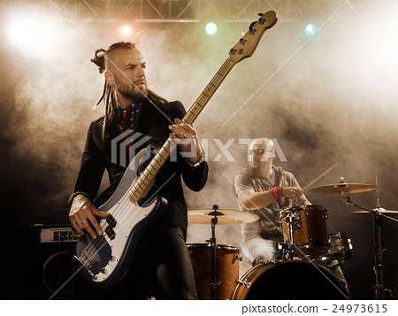 Rock band performs on stage. Bassist in the 24973615