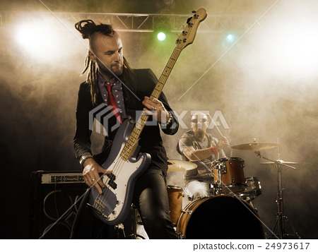 Rock band performs on stage. Bassist in the 24973617