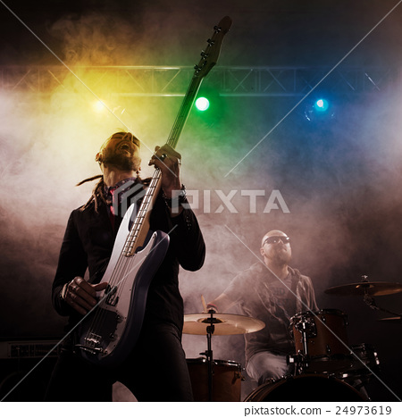 Rock band performs on stage. Bassist in the 24973619