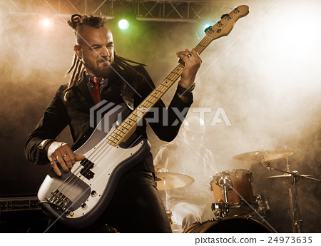 Rock band performs on stage. Bassist in the 24973635