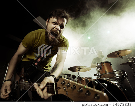 Rock band performs on stage. Guitarist. 24975832