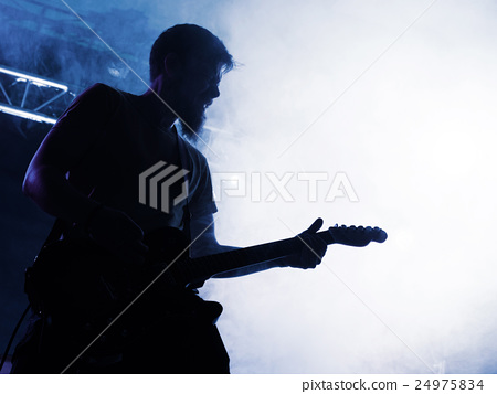 Rock band performs on stage. Guitarist. 24975834