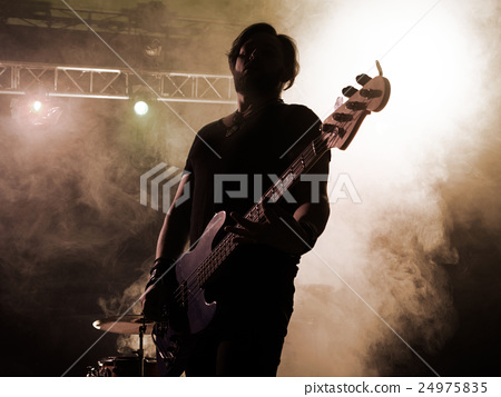 Rock band performs on stage. Guitarist. 24975835